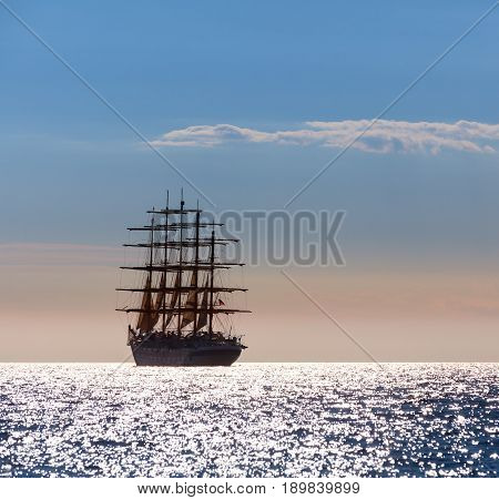 The world's largest sailing ship with five masts leaves at sunset in the open sea.