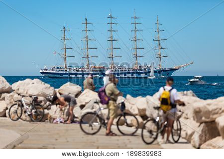 The world's largest sailing ship with five masts anchored in the open sea near old city Piran Slovenia. Tourists on bicycles are looking at the beautiful ship.