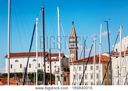 Old city Piran in Slovenia. View vith St. George's Parish Church through masts of yachts moored in a bay. Summer time.