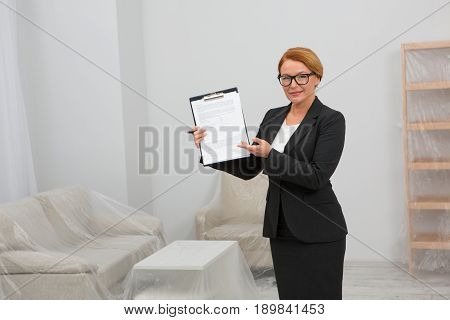 Agreemetn for apartment rent. Realtor agent standing in white room keeping an agreement for rent in her hands. Living room with furniture covered with foil.
