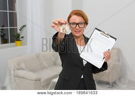 realtor propose to sign an agreement for apartment rent, camera focused on hand keeping keys. Woman in glasses and busines suit standing in the room with keys in one hand and agreement in another.