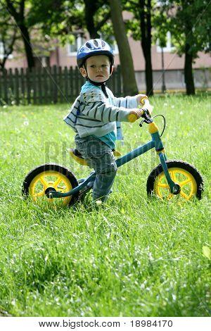 19 Monate alten Baby Boy Reiten auf sein erstes Fahrrad in einen Helm. Fahrrad ohne Pedale. Kind lernen