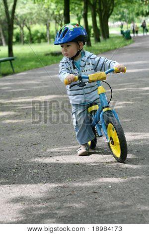 19 Monate alten Jungen Reiten auf seinem ersten Fahrrad in einen Helm. Fahrrad ohne Pedale. Kind lernen