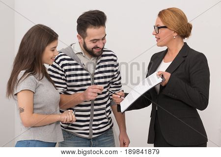 Estate agent pointing to a place in purchase agreement where new owners have to put a signature. Realtor showing agreement to a happy couple.