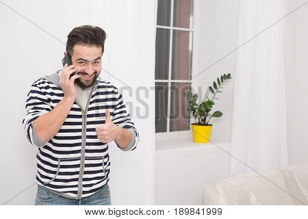 Smiling young man talking on the phone at home.