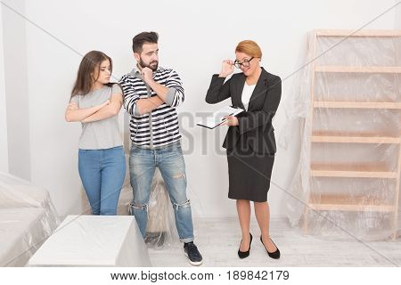 The story about unscrupulous tenants. Agent with documents and young man and woman with unhappy faces in white living room with new furniture.