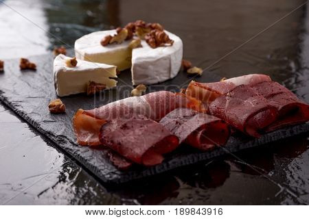 Cheese Camembert With Walnuts And Meat Plate With Walnuts On Black Slate Plate Background.