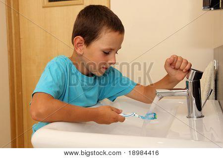 Sechs Jahre alte junge Reinigung Zahn im Badezimmer.
