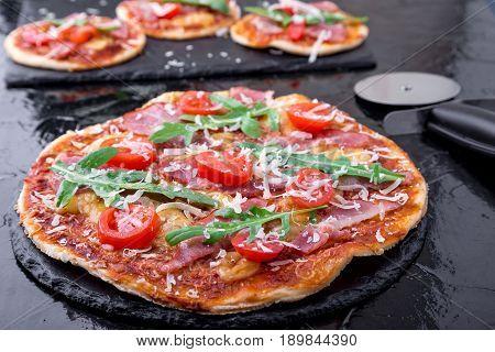 Homemade Pizza With Prosciutto, Tomato, Arugula On Black Slate Board. Close Up.