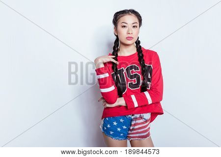 Stylish Hipster Asian Girl In American Patriotic Outfit Posing And Looking At Camera Isolated On Gre