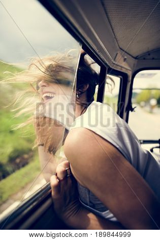 Woman Sitting in a Car Put Head Out of Window Wind Blowing Her Hair