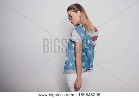 Stylish hipster blonde girl in american patriotic outfit isolated on grey american culture concept