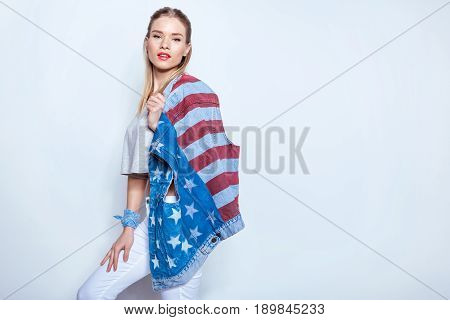 Beautiful blonde girl holding denim vest with american flag on shoulder and looking at camera