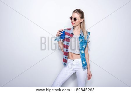 Smiling girl wearing denim vest with stars and stripes and drinking soda from aluminum can