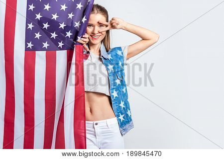 Beautiful Young Woman In Denim Vest With Stars And Stripes Posing With American Flag
