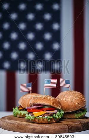 Three Cheeseburgers With Little American Flags On Wooden Board, Us Flag On Background, American Cult