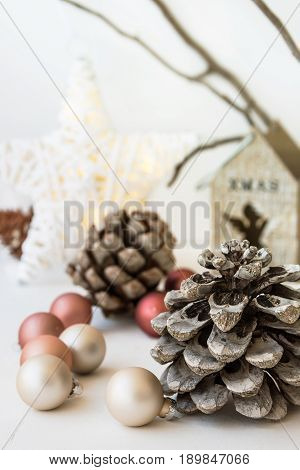 White Christmas decoration composition big pine cones scattered baubles shiny star wooden candle holder dry tree branches in background scandinavian style