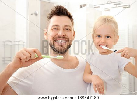 Young father with his daughter brushing teeth in bathroom