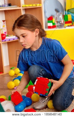 Children building blocks in kindergarten. Group kids playing toy on floor. Top view of interior preschool. Child misses parents