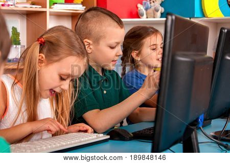 Children computer class us for education and video game. Boys and girls in children's club who spend many hours behind computer monitor harmful to health. Children play on the computer. Simulator for