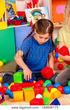 Children building blocks in kindergarten. Group kids playing toy on floor. Top view of interior preschool. Kid is keen on playing dice.