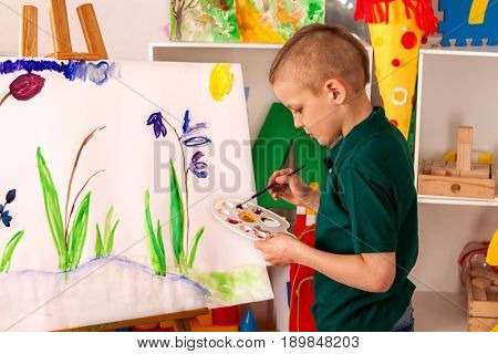 Child painting on easel. Kid boy learn paint by brush in class school. Kindergarten interior on background. Boy is getting ready to become an artist.