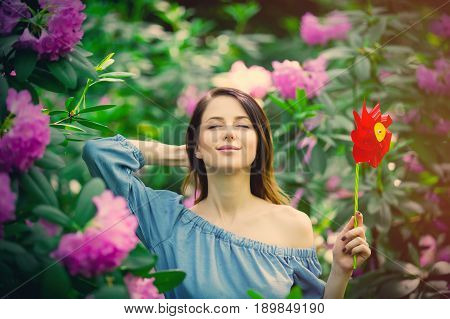 Woman With Pinwheel In Blossom Garden
