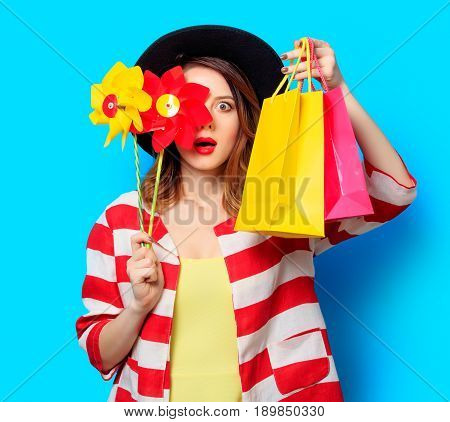 Woman With Pinwheel And Shopping Bags