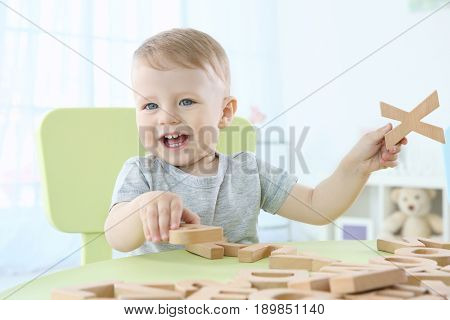 Cute little child playing with letters at home