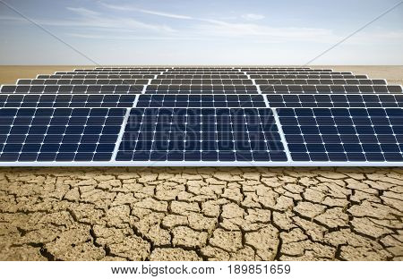 Many solar panels in cracked desert land