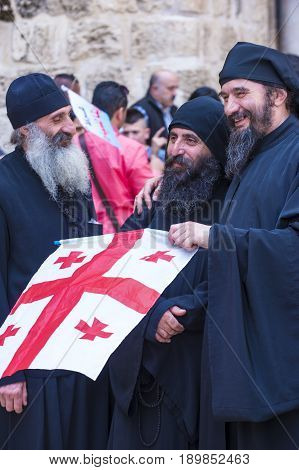 JERUSALEM - APRIL 14 : Christian pilgrims carry flag along the Via Dolorosa in Jerusalem on April 14 2017 commemorating the path Jesus carried his cross on the day of his crucifixion