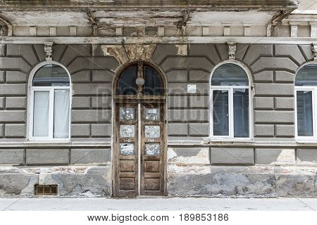 Old Dirty Wooden Door With Cracked Wall And Windows