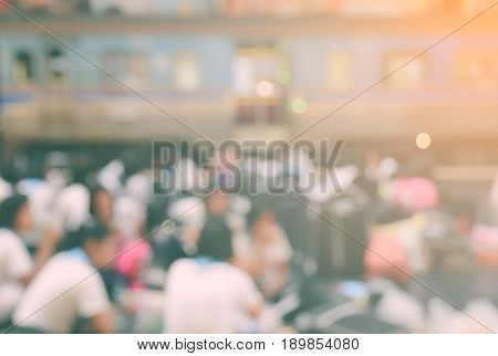 Crowded station with passenger train. Blurred passengers with train background.