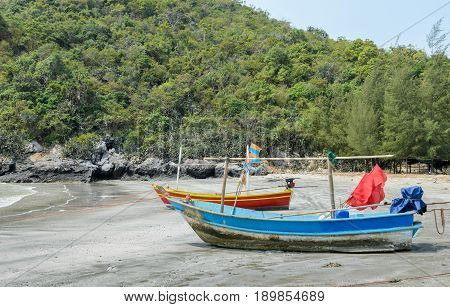 Small woodenl fishing boats (Longtail boats) anchored on beach at low tide in Thailand