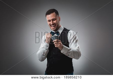 Young man in shirt and waistcoat watch his poker cards, studio shot. Poker. Emotions