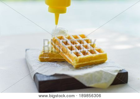 Close up syrop put on top of belgian waffles