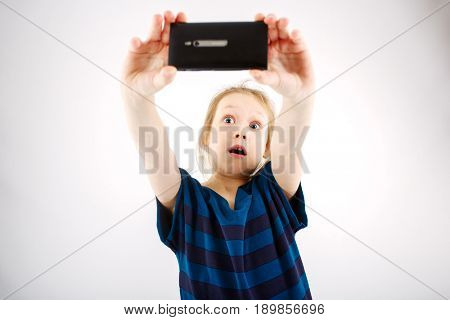 A little girl shoots on a smartphone