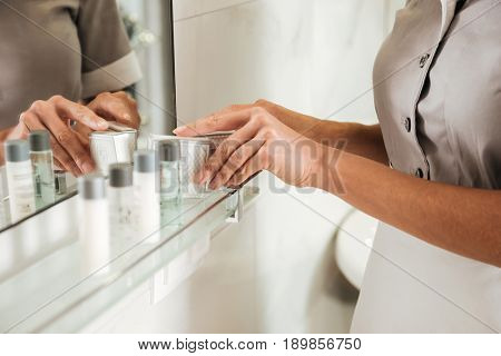 Close up of a young hotel maid putting bath accessories in a bathroom