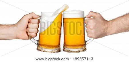 hands with mugs of beer toasting creating splash isolated on white background. Pair of beer mugs making toast. Beer up. Male hands holding mug of light beer toasting. Cheers