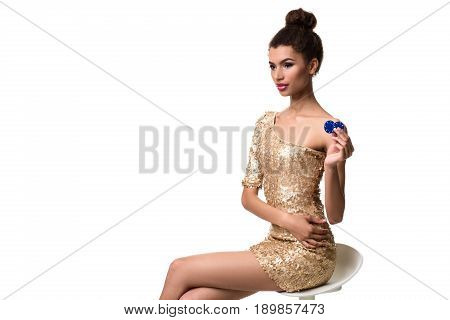 Beautiful young woman holding two chips in her hand isolated on white. A woman is sitting on a white chair without a backrest. Studio shot. Poker
