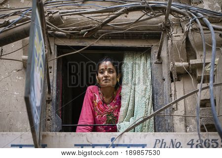 KATHMANDU NEPAL - SEPTEMBER 28 2016 : Nepalese woman looks out of a window to the street in Kathmandu Nepal