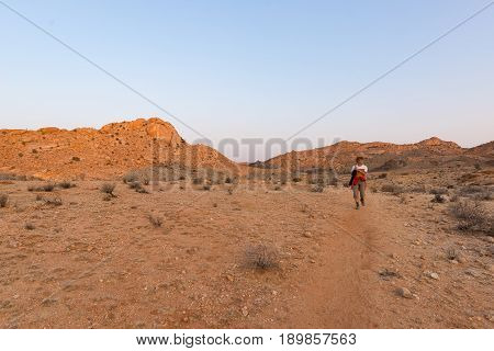 One person hiking in the Namib desert Namib Naukluft National Park Namibia. Adventure and exploration in Africa. Clear blue sky.