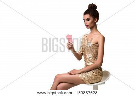 Beautiful young woman holding two cards in her hand isolated on white. A woman is sitting on a white chair without a backrest. Studio shot. Poker