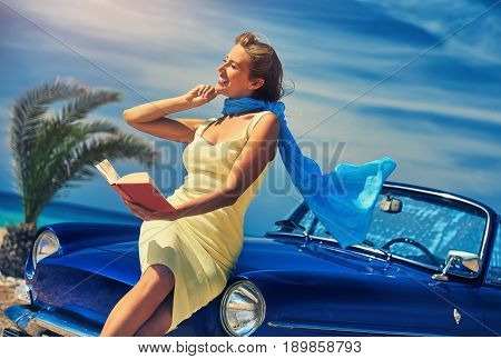 Beautiful happy woman reading a book near retro cabriolet car on the beach. Idyllic scenery