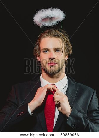man with halo. man with white feather halo above head businessman in suit and tie on black background