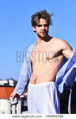 Bearded man short beard. Caucasian macho with moustache and ruffled hair in blue striped pajamas holding cup or mug in roof and showing strong torso with six packs on blue sunny sky background