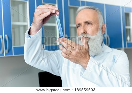 Pensive Senior Bearded Chemist In White Coat Holding Tube With Reagent In Chemical Laboratory