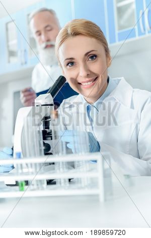 Caucasian Smiling Scientist In White Coat Working With Microscope And Reagents While Looking At Came