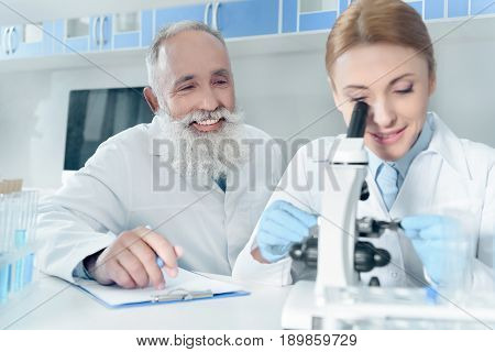 Two Happy Scientists In White Coats Working Together With Microscope In Chemical Laboratory