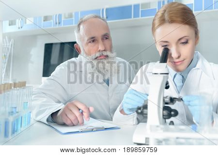 Two Scientists In White Coats Working Together With Microscope In Chemical Laboratory